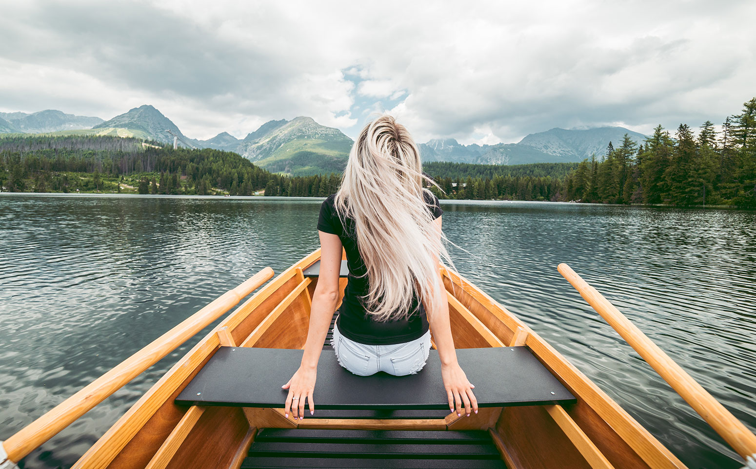 Young Blonde Woman Enjoying a Rowing Boat